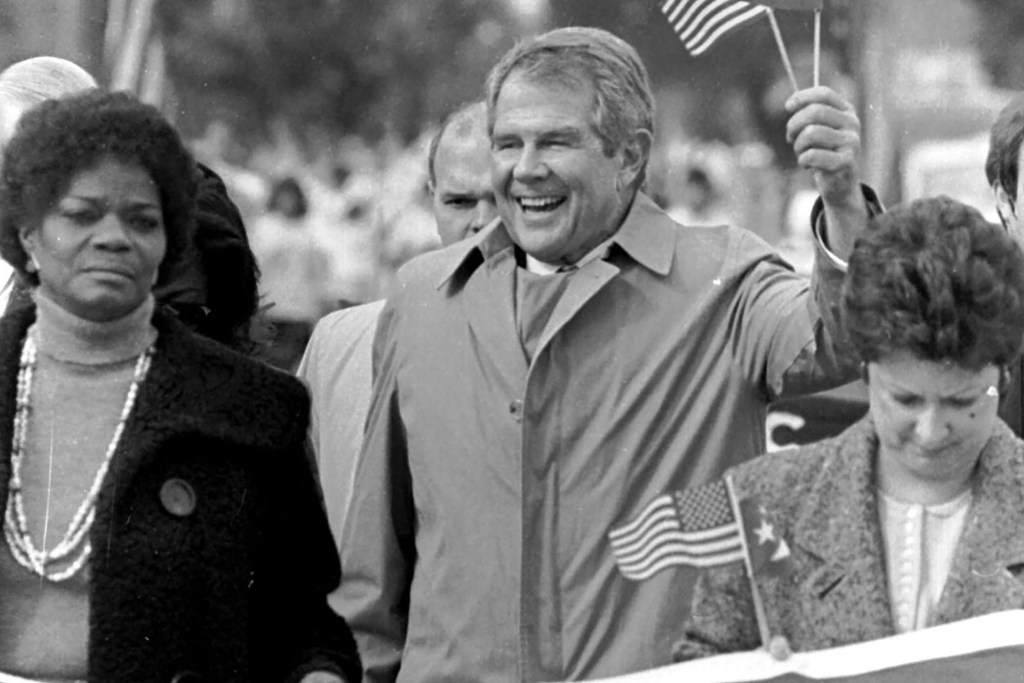Pat Robertson waves American and Cuban flags on a presidential campaign trip to Miami in January of 1988.