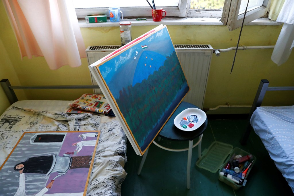Paintings of an Afghan refugee, Murad Sharifi, are seen in his room in a homeless shelter in Budapest, Hungary, September 27, 2021.