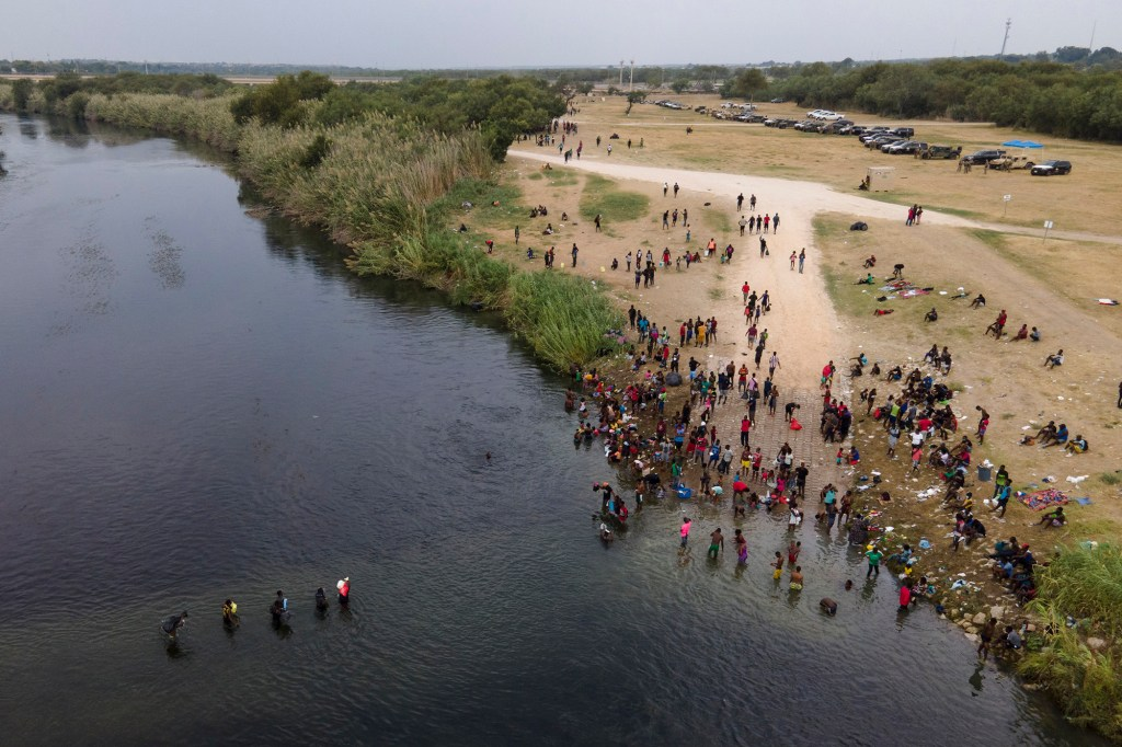 Migrants, many from Haiti, are seen wading between the U.S. and Mexico on the Rio Grande, in Del Rio, Texas.