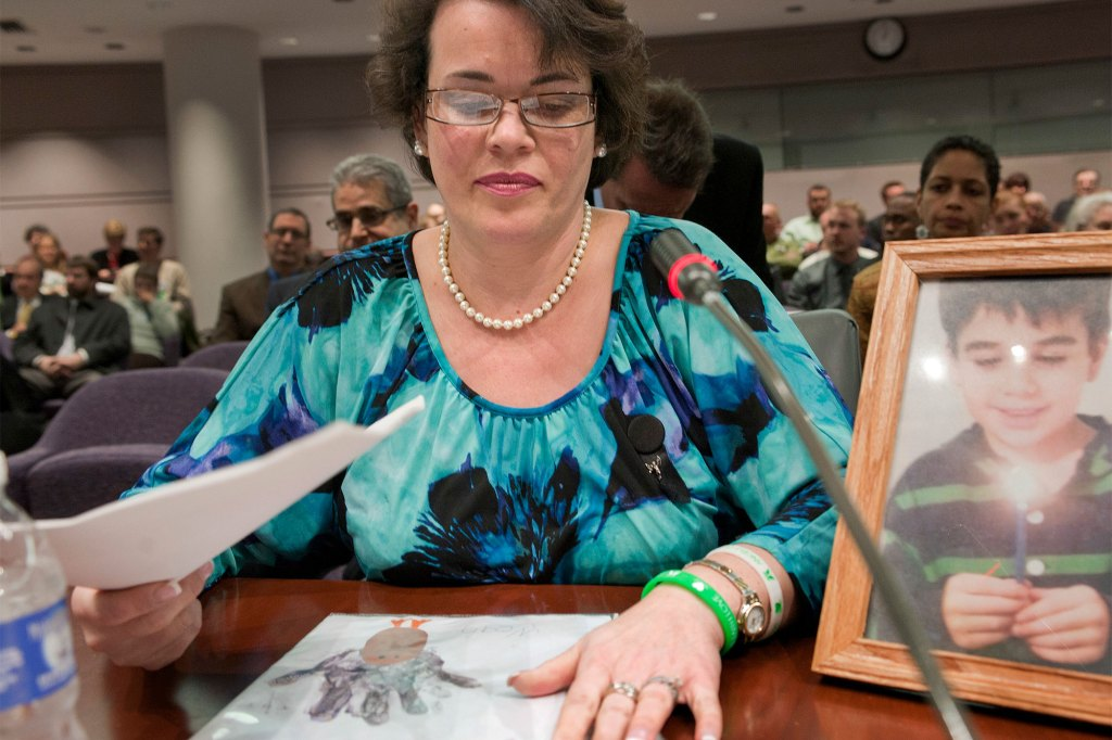 Veronique Pozner places her hand next to artwork made by her son Noah before testifying before a hearing of a legislative subcommittee reviewing gun laws at the Legislative Office Building in Hartford, Conn., on Jan. 28, 2013.