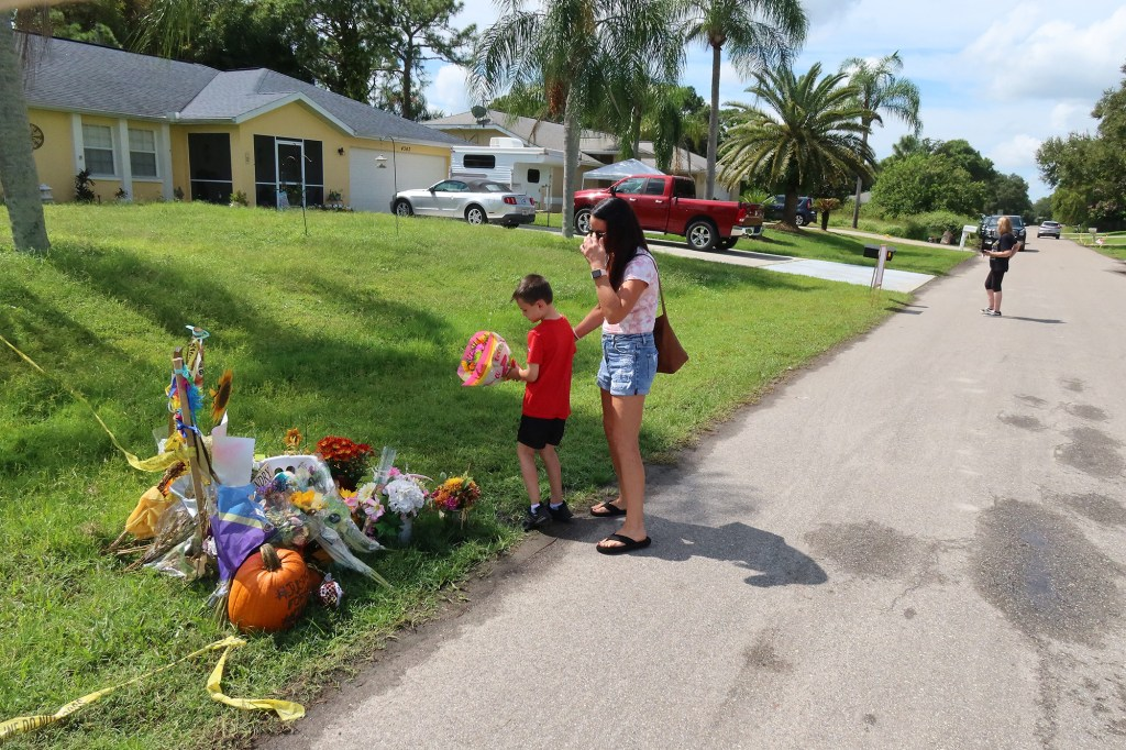 Alicia Dempsey and her son Anthony Orlando lay flowers at the Memorial for Gabby Petito in front of Brian Laundrie's home.