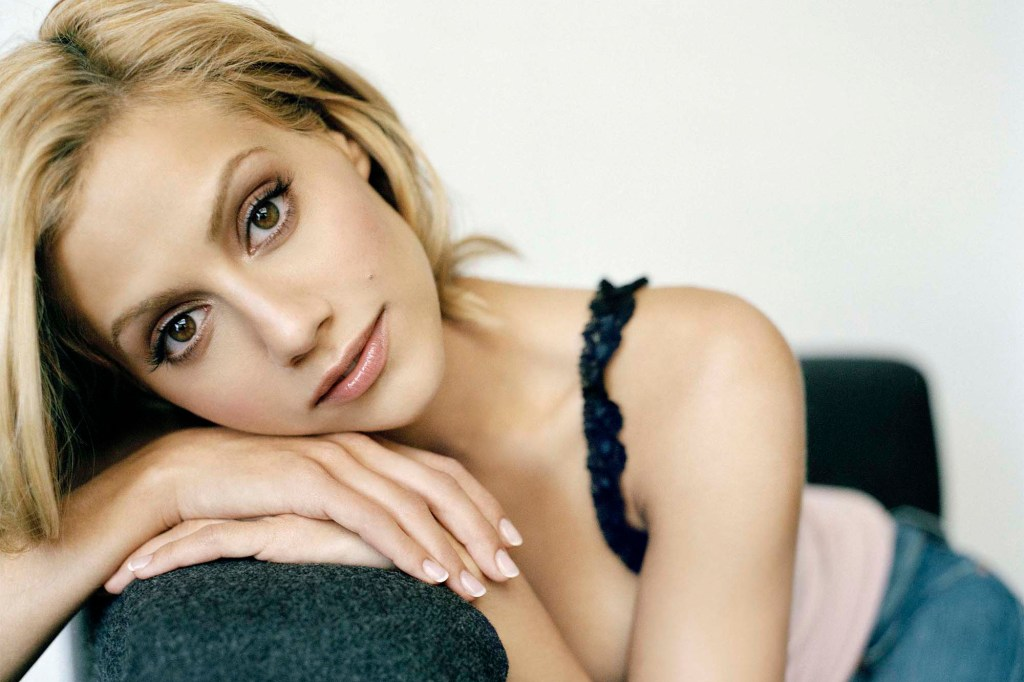 A blonde Brittany Murphy gazes pensively at the camera resting her face on her hands.