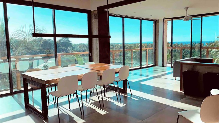 The dining room offers vast views through floor-to-ceiling windows.