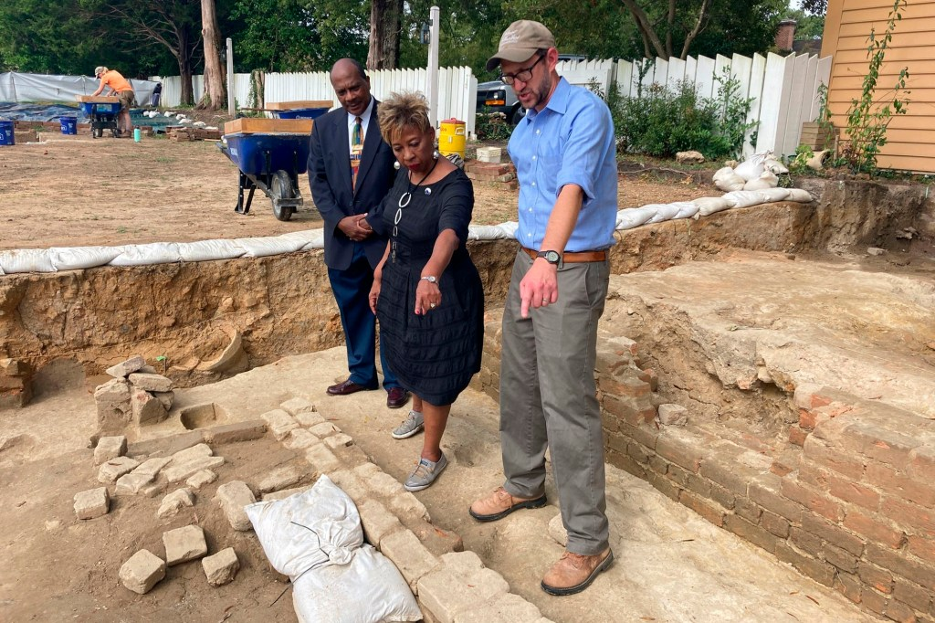 Reginald F. Davis, from left, pastor of First Baptist Church in Williamsburg, Connie Matthews Harshaw, a member of First Baptist, and Jack Gary, Colonial Williamsburg's director of archaeology, stand at the brick-and-mortar foundation of one the oldest Black churches in the U.S. on Wednesday, Oct. 6, 2021, in Williamsburg, Va.