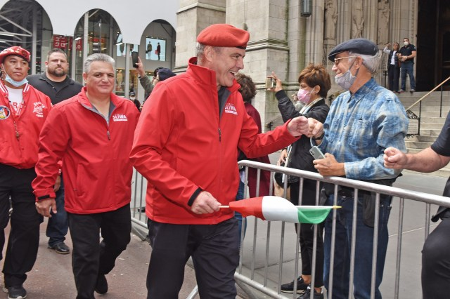 Curtis Sliwa bumps fists with people along the parade route.