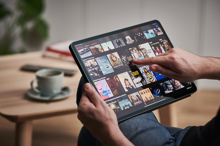 A person holding a tablet, which shows a host of movies.