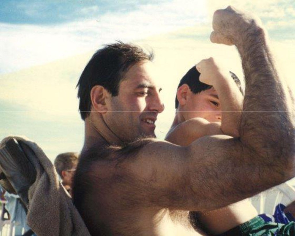 Nate Ebner flexes his muscles as a boy with his father, Jeff.