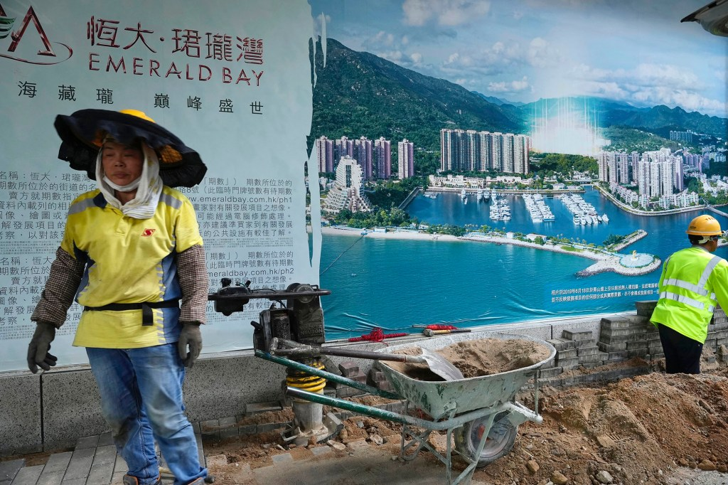 A worker walks past an advertisement photo of a property project of China Evergrande Group outside its headquarters in Hong Kong.