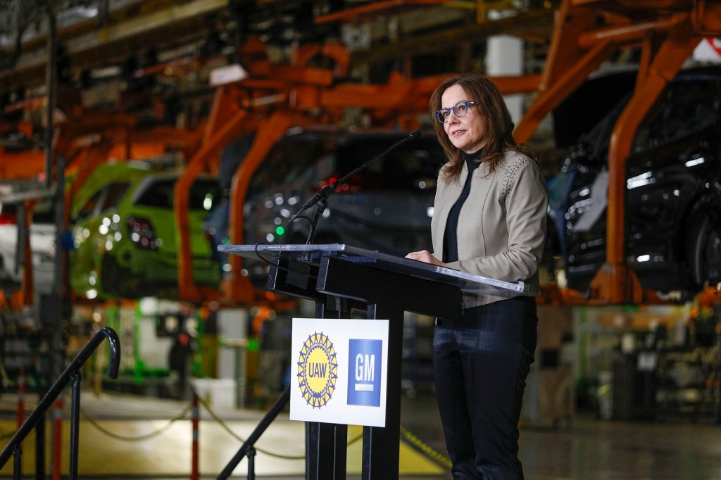 Mary Barra speaking at a podium with the logos of GM and of the United Auto Workers