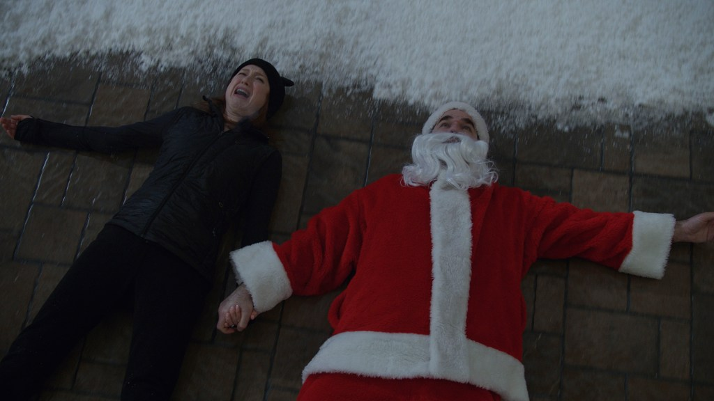 Ellie Kemper and Rob Delaney on their backs in the snow in Home Sweet Home Alone