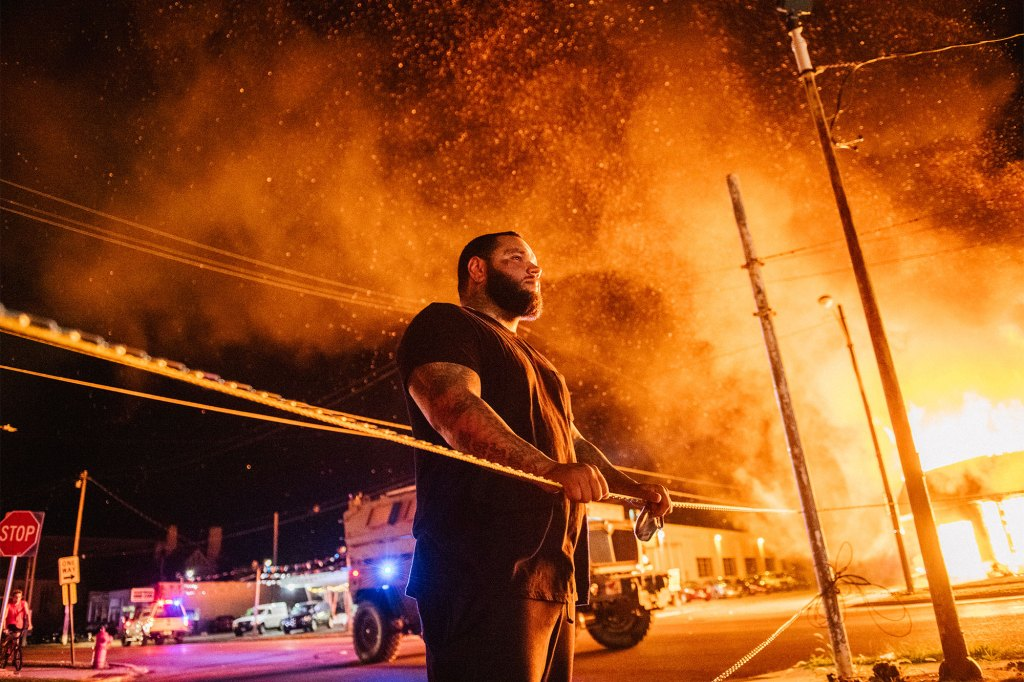 A man looks over caution tape during a second night of civil unrest in Kenosha, Wisconsin on August 24, 2020.