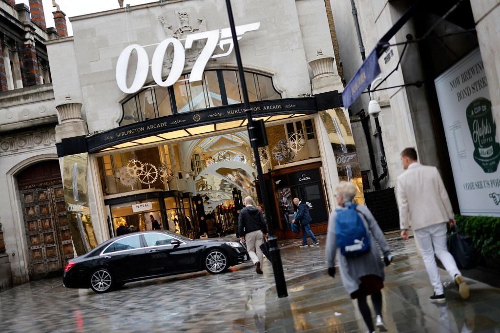 A pedestrian walks past a James Bond 007 logo above the entrance to Burlington Arcade in London