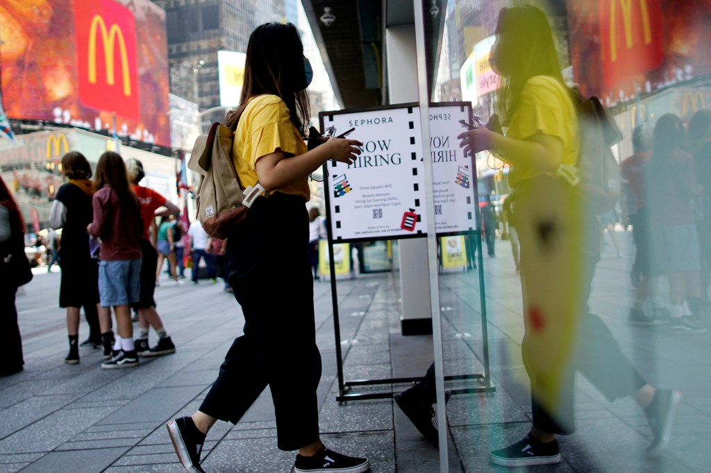 A woman enters a store next to a sign advertising job openings at Times Square