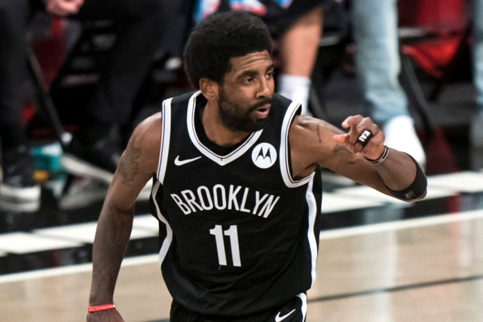 Kyrie Irving points on the court during a Brooklyn Nets-Milwaukee Bucks playoff game in 2021.