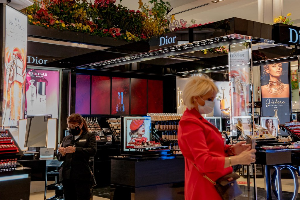 A woman shopping at the beauty counters at Macys.