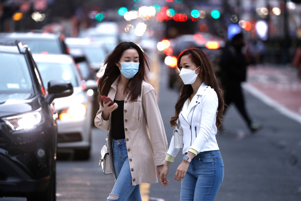 Women wearing protective masks cross the street in Midtown on March 27, 2021 in New York City.