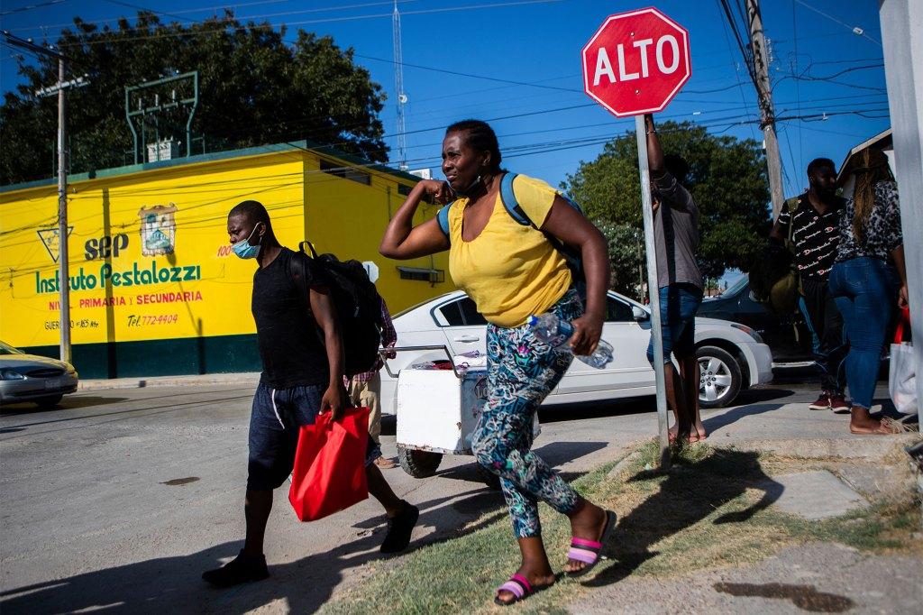 Haitian migrants walk toward the Rio Grande river to return to the migrant encampment in Del Rio, Texas.