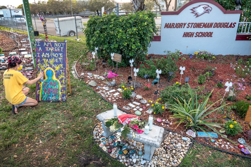 Victoria Rosa paints a poster in honor of the Parkland shooting victims in the makeshift memorial in front of the Marjory Stoneman Douglas High School in Parkland, Florida, USA, 11 February 2021