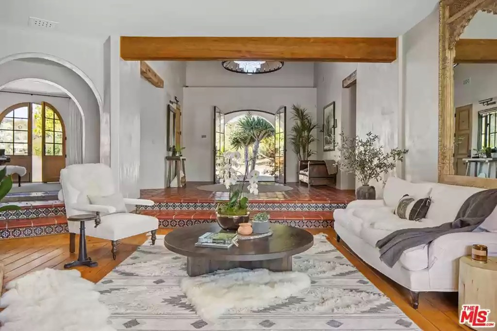 Authentic Spanish tiles and arched doorways are pictured in the great room.