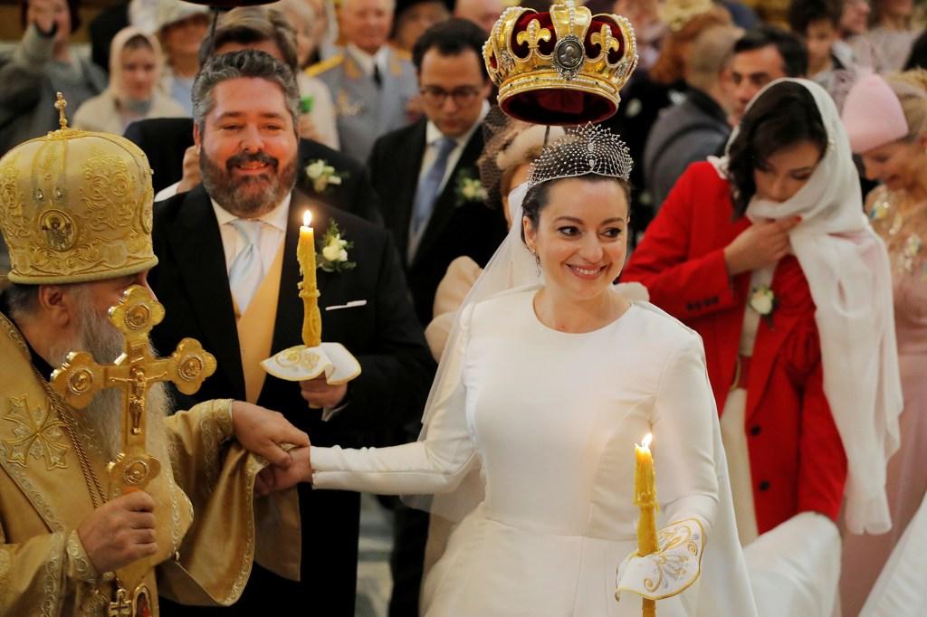 Grand Duke George Mikhailovich Romanov and Victoria Romanovna Bettarini follow Metropolitan Varsonofius of Saint Petersburg and Ladoga during their wedding ceremony.