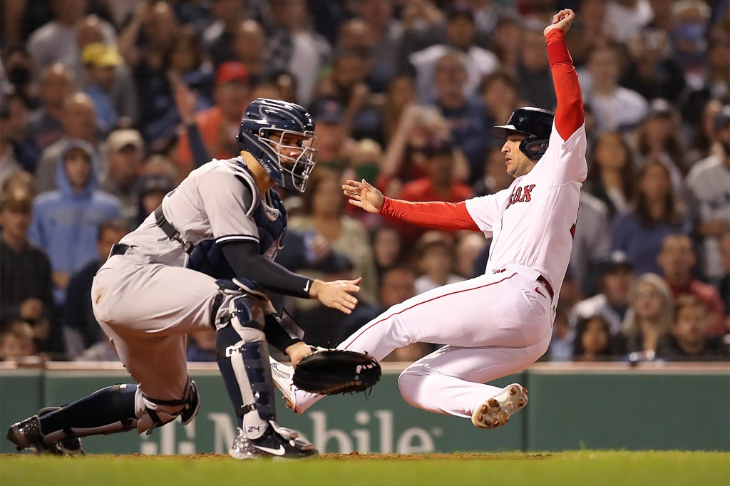 Jose Iglesias of the Boston Red Sox is safe at home as he beats the throw to New York Yankees catcher Gary Sanchez.