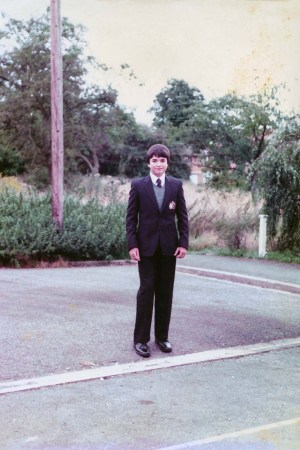 Simon Monjack as a young teen boy stands on a sidewalk wearing a suit.