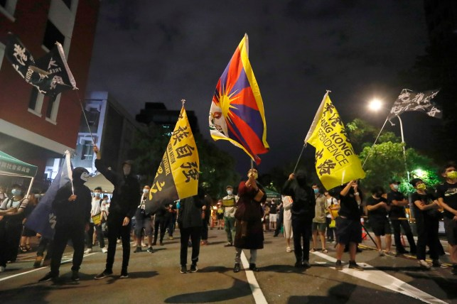 Protesters in Taiwan hold up signs reading anti-Chinese dictatorship.