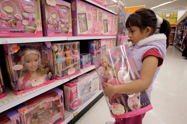 A child is holding a doll in a toy section.