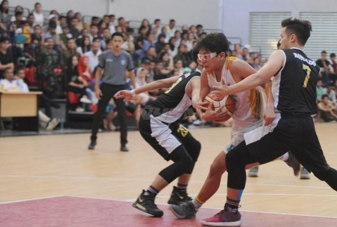 Dua pemain Tim Basket Kabupaten Tangerang (hitam) mengepung pemain Kota Tangerang Selatan (Tangsel), dalam laga final Bola Basket POPDA IX/2018, Rabu (9/5). (Pras/NYSN)