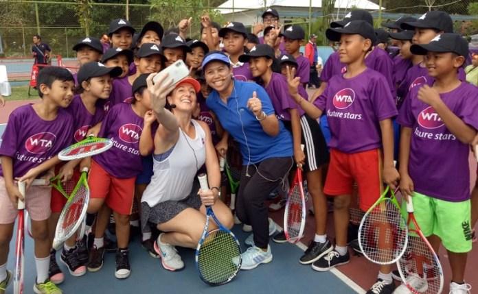 Legenda tenis Indonesia, Yayuk Basuki (biru) yang menjadi Duta WTA Finals, memperkenalkan tenis kepada 50 anak berusia 10-12 tahun, dari Yayasan Sosial Tat Twam Asi, Denpasar. (menaranews.com)