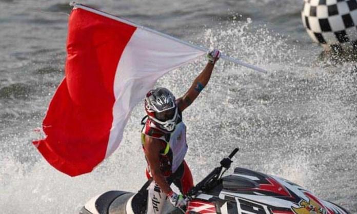 Atlet jetski Indonesia, Aqsa Sutan Aswar, mengibarkan bendera merah putih setelah meraih medali emas dari nomor endurance runabout open cabor jet ski, di Jetski Indonesia Academy Ancol, Minggu (26/8). (tempo.co)