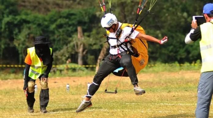 Atlet paralayang Indonesia, Joni Efendi, saat melakukan landing, dalam nomor ketepatan mendarat (KTM) beregu putra cabor Paralayang atau Pragliding, di Gunung Mas Puncak, Bogor, Rabu (22/8). (liputan6.com)