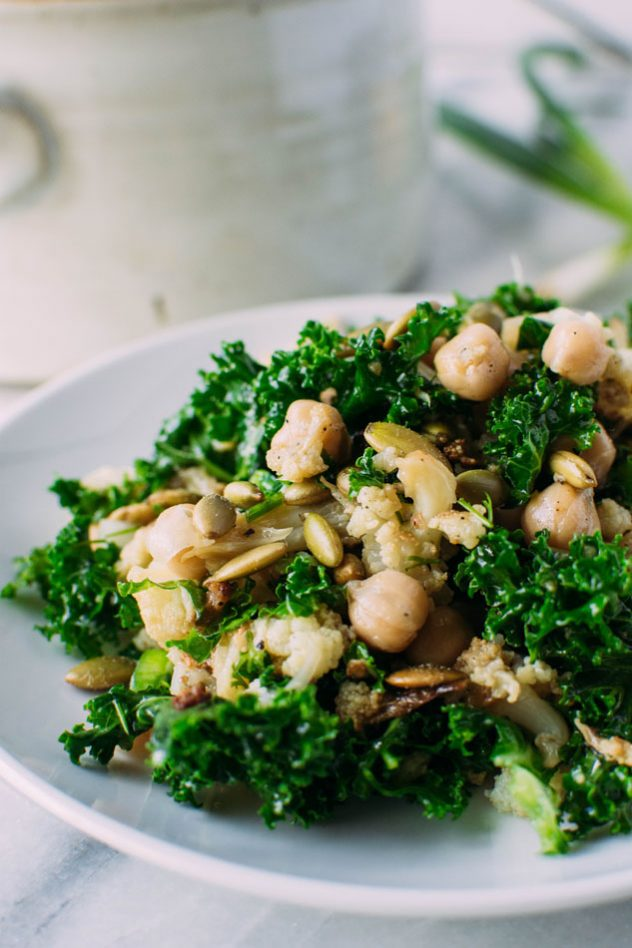 chopped winter detox salad with roasted cauliflower + chickpeas + kale! Gluten free, vegan and easily made paleo by substituting the chickpeas for some chicken or turkey, this hearty and healthy winter salad is the perfect clean salad to tuck into your fridge and enjoy all week long!