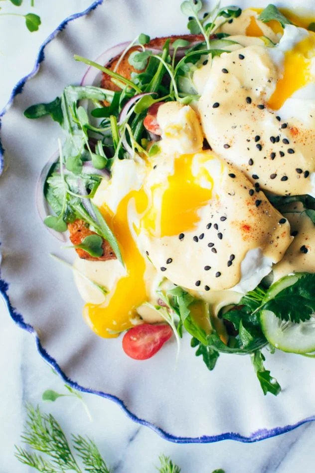 Paleo mediterranean eggs benedict made with layers of spiced sweet potato planks, a bright + tangled lemony salad of arugula, cherry tomatoes, cucumber and red onion, perfectly poached eggs and a paprika spiked tahini hollandaise sauce.
