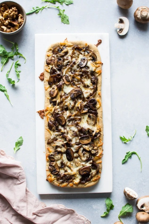 This grain free caramelized onion and mushroom pizza with arugula is made with Simple Mills almond flour pizza dough, topped with flavorful caramelized onions and mushrooms, smoked mozzarella cheese, and a peppery + bright arugula and toasted walnut salad -basically making it the ideal healthy pizza situation!
