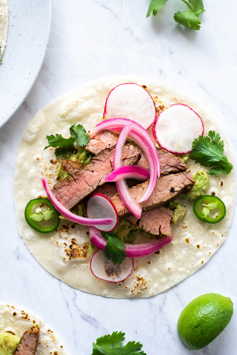 A close up shot of a steak taco on a white background with cilantro, thinly sliced jalapeno, pickled red onions