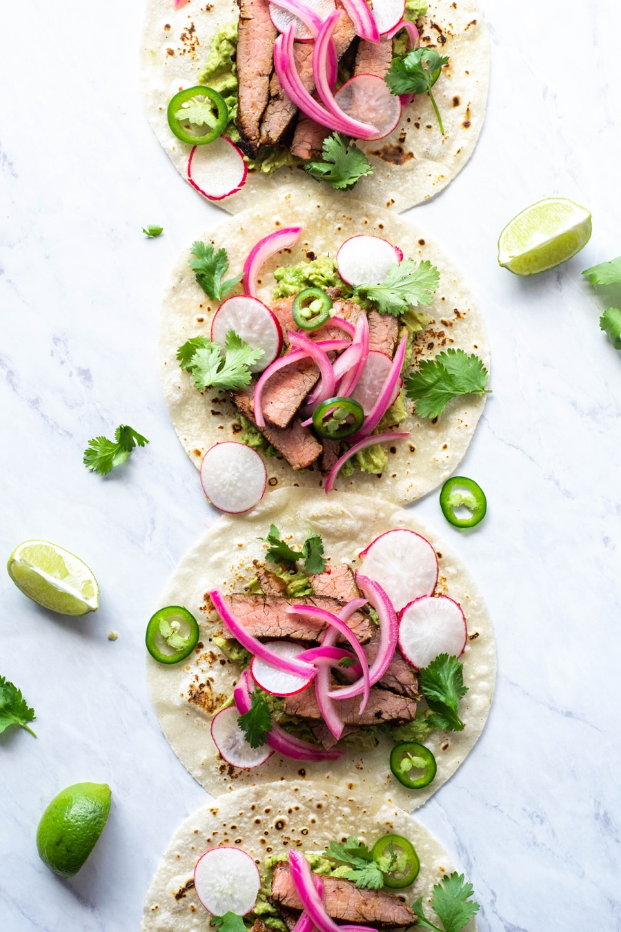 Multiple steak tacos lined up from the top to the bottom of the image on a white background with cilantro, thinly sliced jalapeno, pickled red onions
