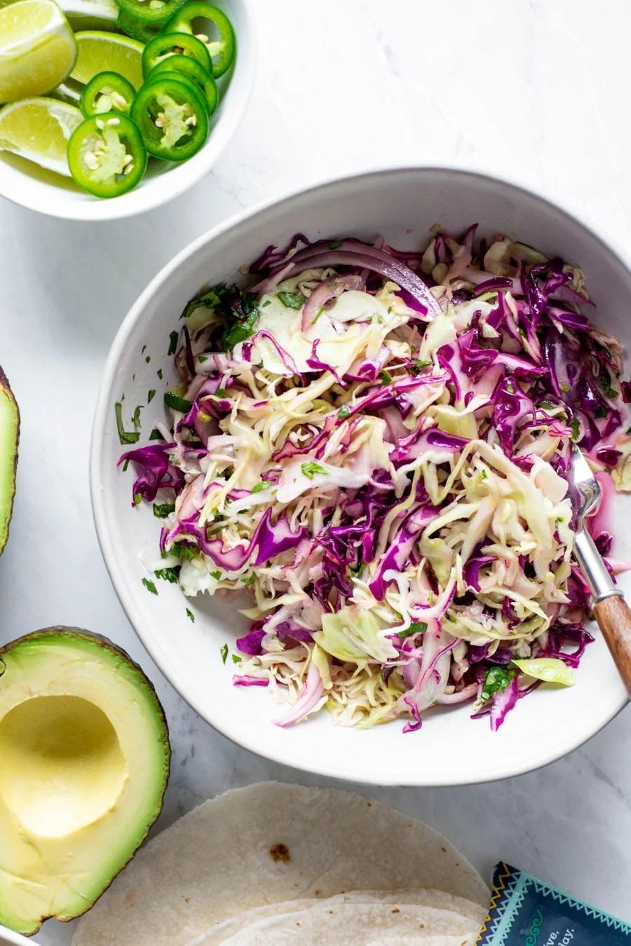 Close up of a bowl of cabbage and red onion slaw for mexican roasted cauliflower tacos