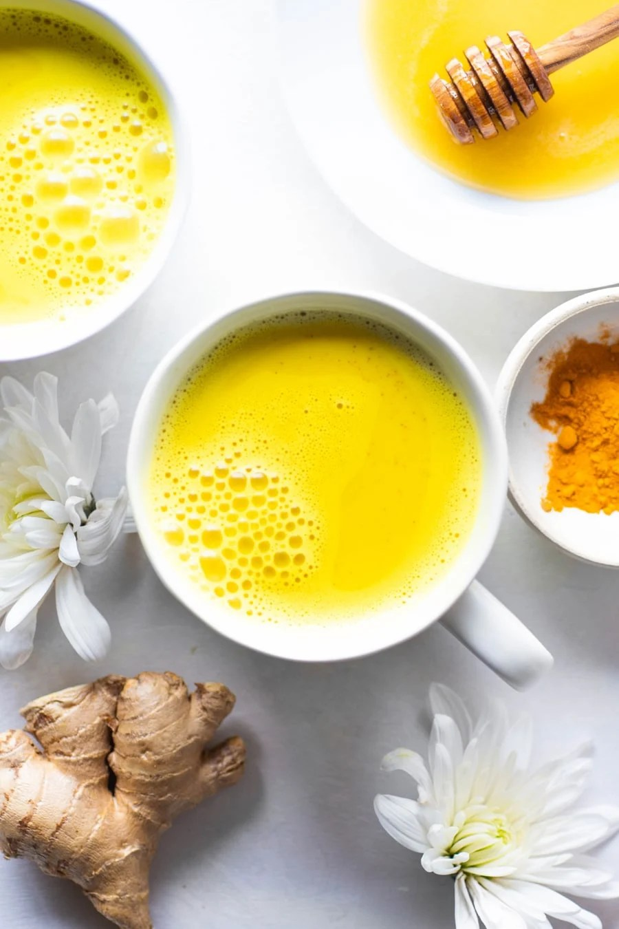Bright yellow golden milk latte in a white mug with white flowers and fresh ginger