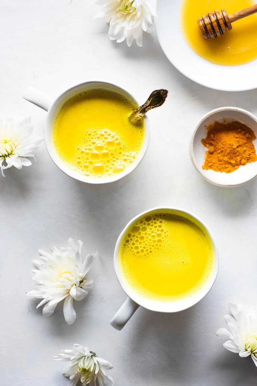 Two bright yellow golden milk latte in a white mug with white flowers and a small bowl of turmeric