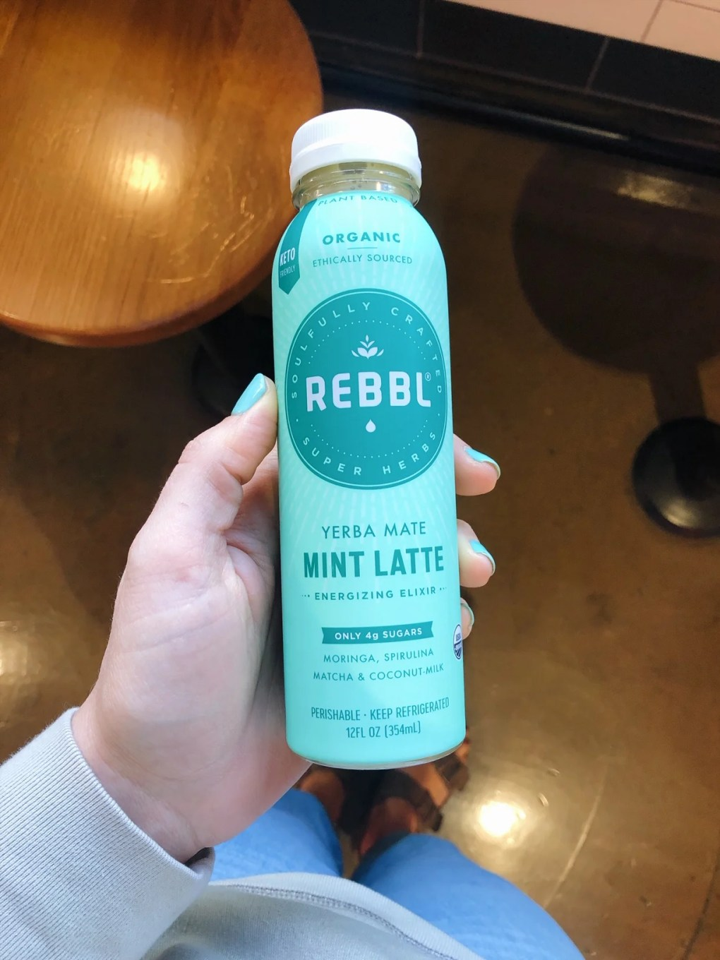 Holding a Chocolate mint Rebbl drink in the grocery store