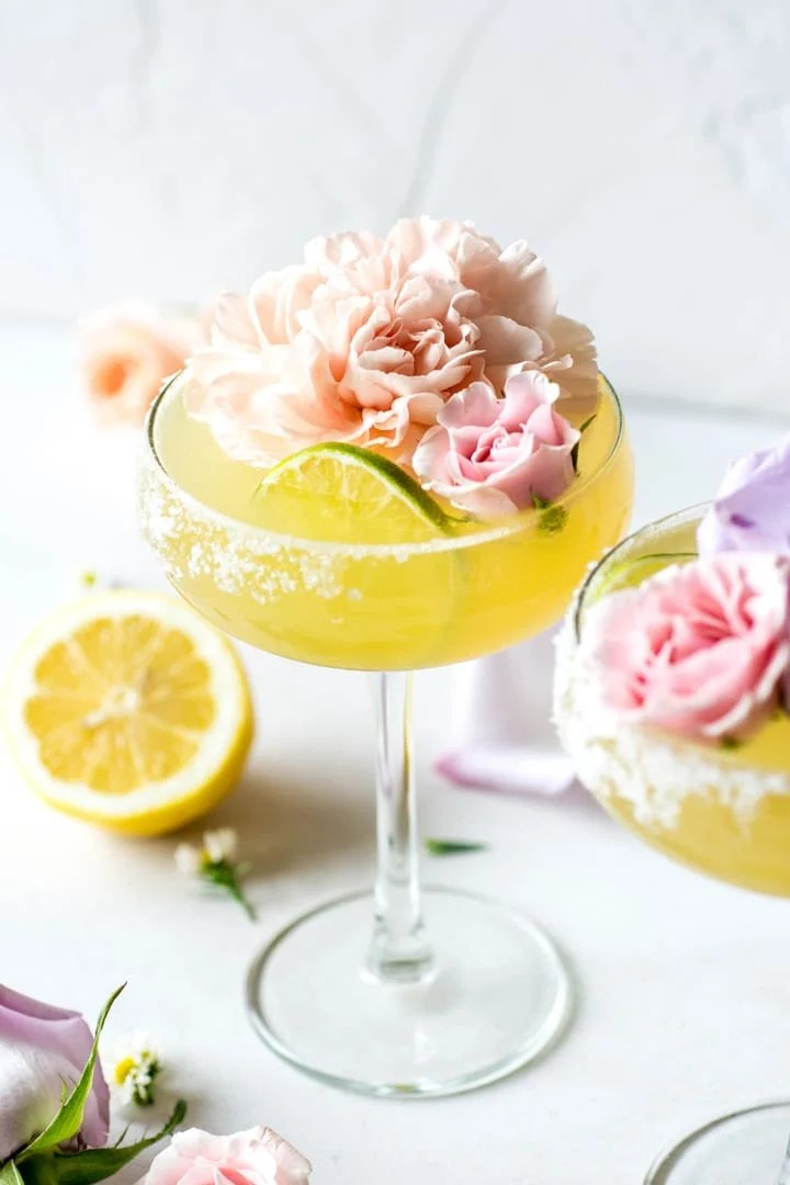 A side view of a bright yellow kombucha margarita served up with a big pink flower and a lime wheel.
