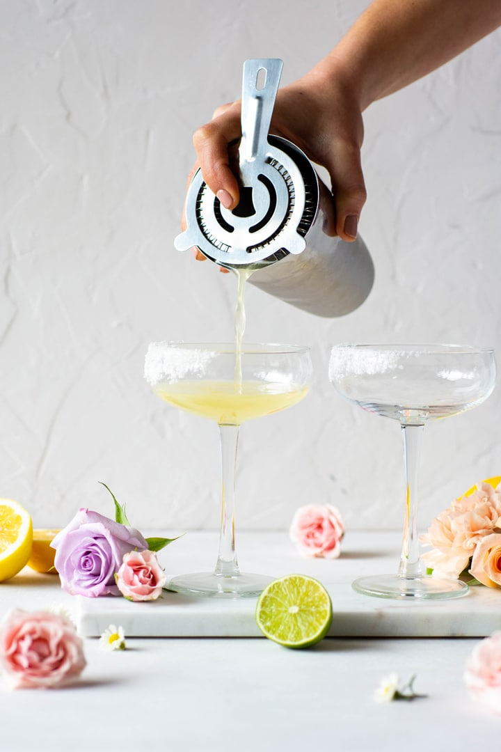 Pouring margarita into a coupe cocktail glass with a cocktail mixer surrounded by citrus and flowers