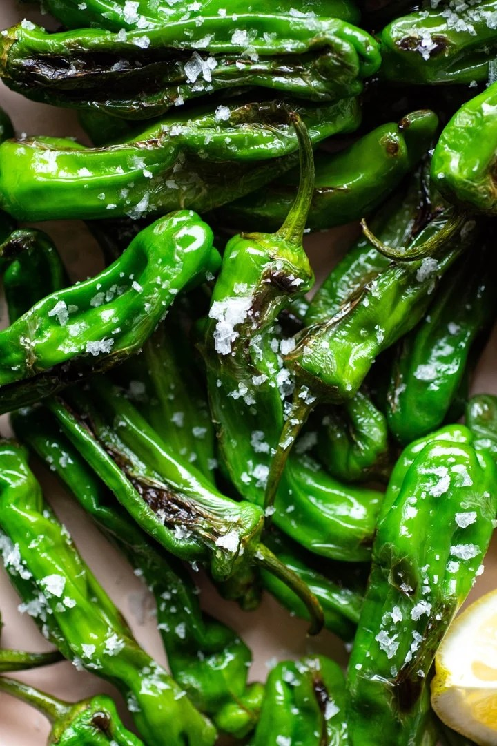 Super close up of blistered shishito peppers with flaky sea salt