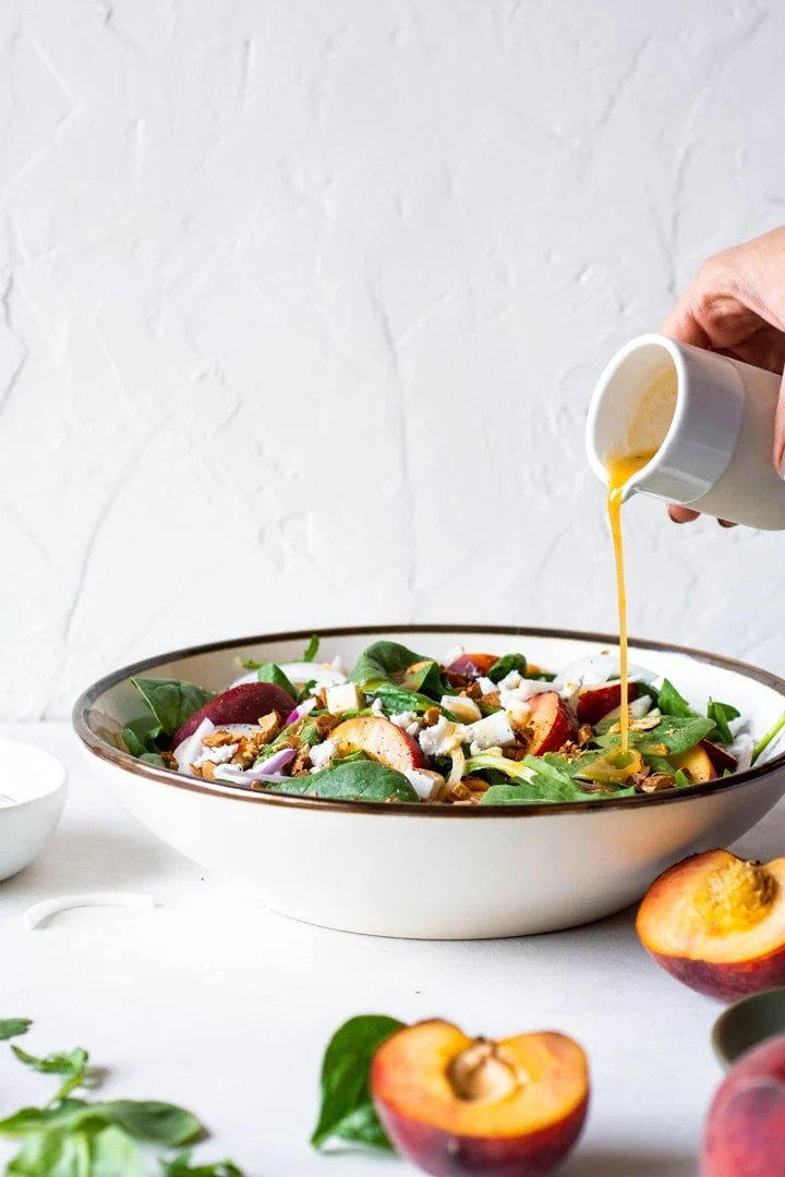Side view of a large bowl of green salad with peaches, chopped almonds, sliced onion, and crumbled feta cheese. Hand pouring salad dressing over the salad.