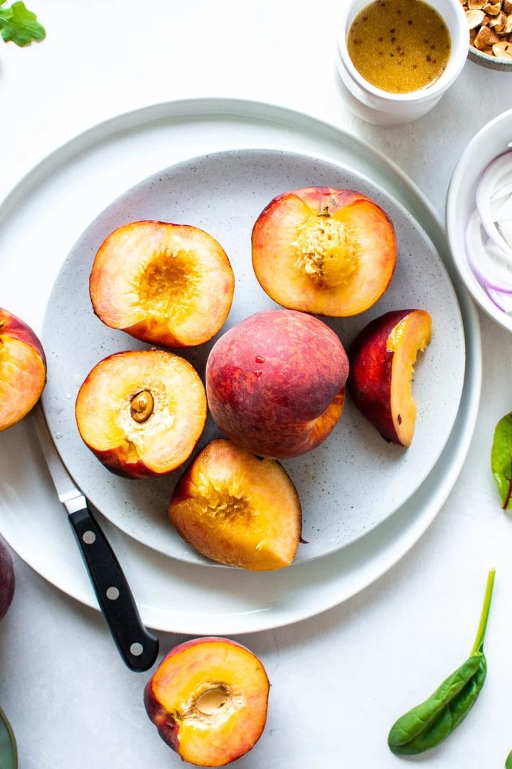 A white plate of halved and whole peaches on top of another white plate on a light colored background next to a jar of dressing, a small bowl of red onions, and a few green salad leaves.