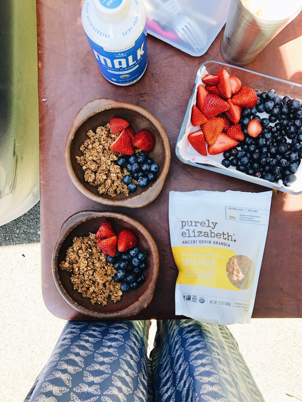 Granola and berries in two small brown bowls  on a brown folding table next to a bowl of berries and a bag of granola