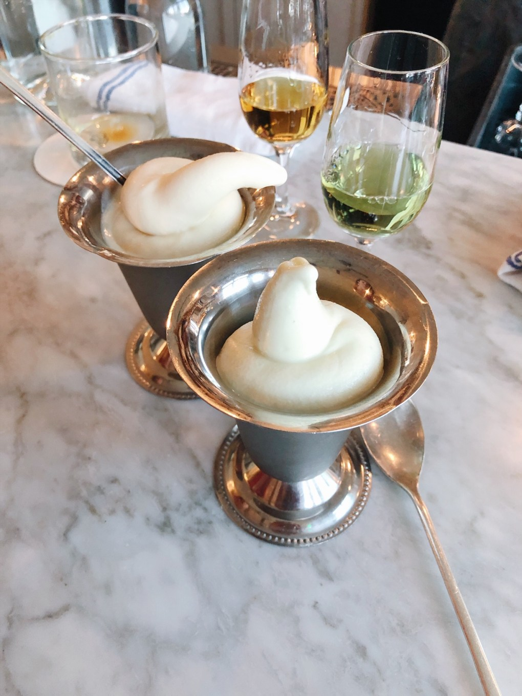 Two metal dishes of soft serve on a bar top next to two glasses of digestifs