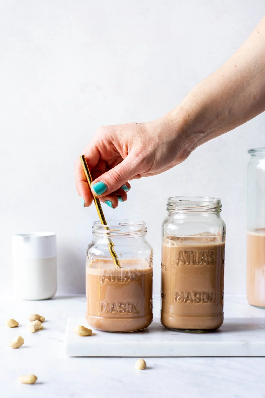 Placing a straw in one of two side by side glasses of chocolate cashew milk on a white background