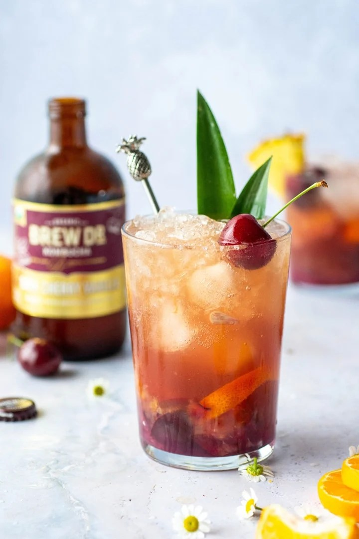 A tropical cocktail with pineapple leaves and a cherry on a light blue background in front of a bottle of Brew Dr. Dark cherry vanilla Kombucha